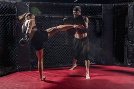 Man and woman MMA Fighters training in octagon