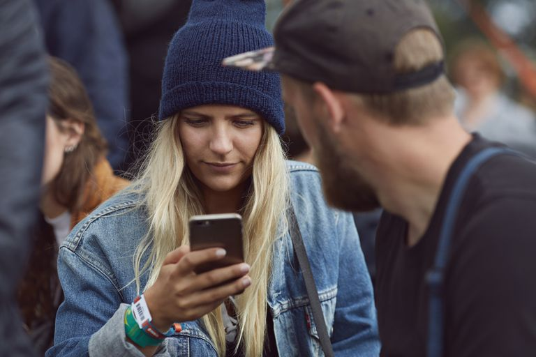 woman looking at her phone in front of boyfriend