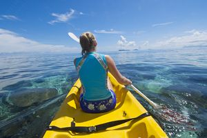A woman paddling a Sit on Top Kayak to go snorkeling at the home reef of Tokoriki Island, Fiji.