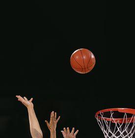 A basketball flying toward a hoop
