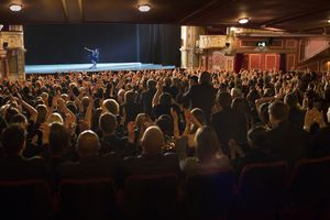 Audience applauding ballerina on stage in theater