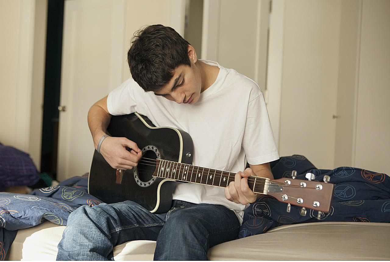 Teenaged boy sitting on his bed playing a guitar