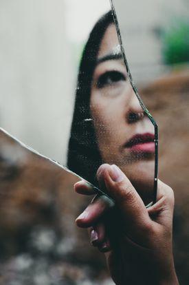 Woman reflected in broken mirror