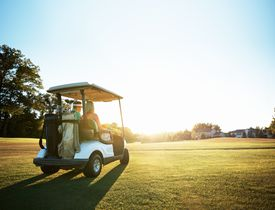 Two golfers sitting in a buggy on a golf course.