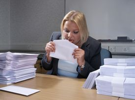 Young businesswoman licking envelope seal at desk