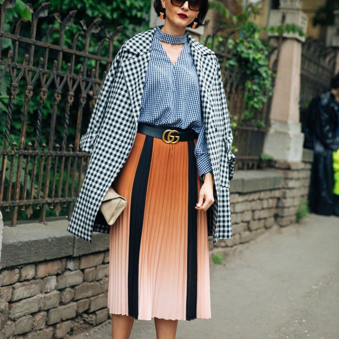 Woman wearing a gingham coat and top with a pleated skirt in orange and black