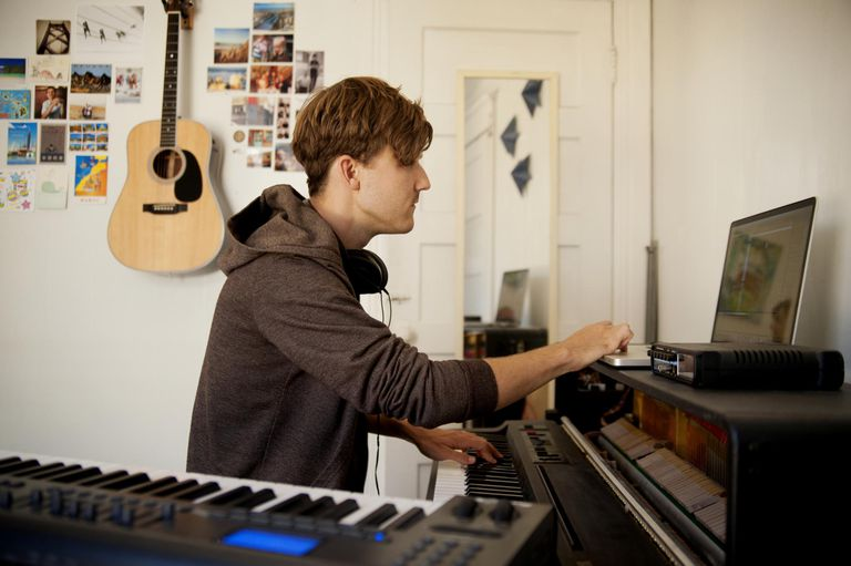 Young Man Playing Music In Bedroom
