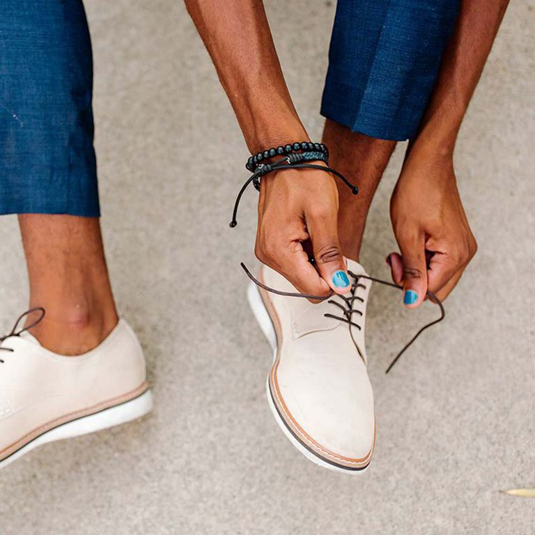 closeup of person tying shoes