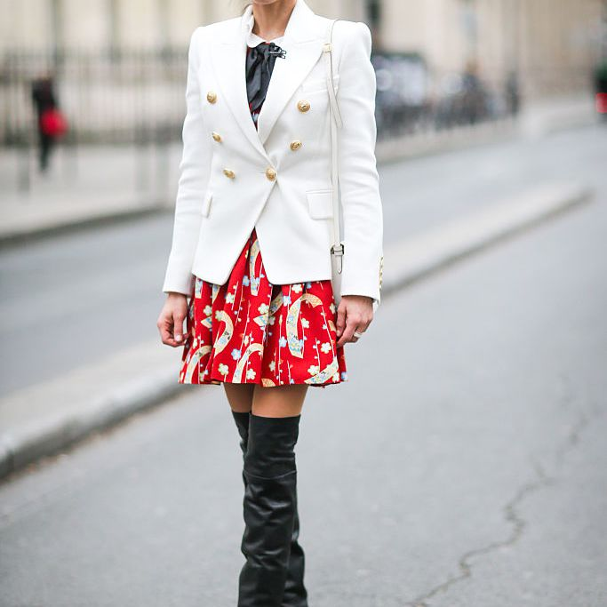 Woman in white blazer and skirt and tall boots