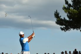 With a short, high follow-through, Tiger Woods plays a knockdown shot off the tee.