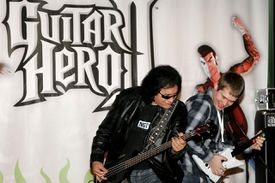 Musician Gene Simmons plays guitar with Guitar Hero II champion J.W. McNay at Virgin Megastore in Times Square to help launch Guitar Hero II on XBOX 360 on April 11, 2007 in New York City