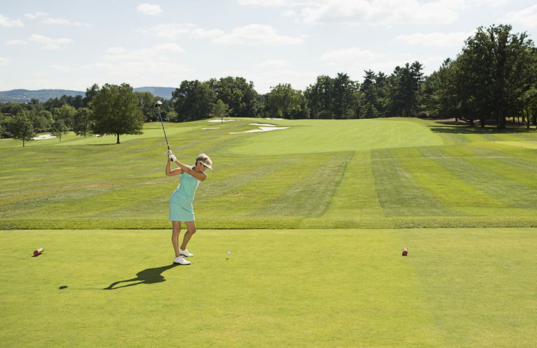 Woman tees off from the forward tees at a golf course