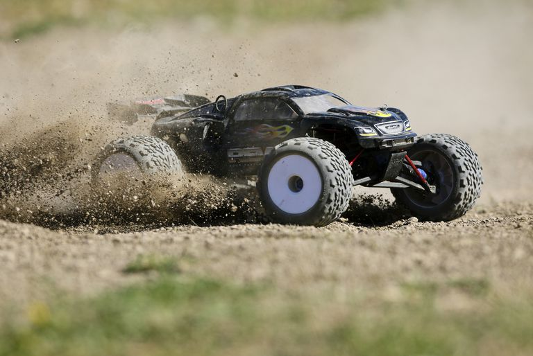RC car zooming by in a cloud of dust