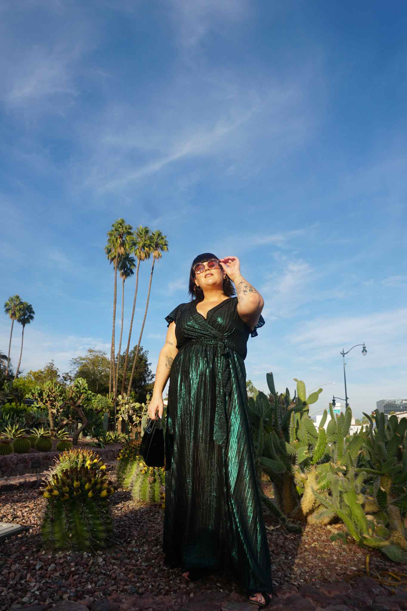 Woman in a green metallic maxi dress against outdoor background