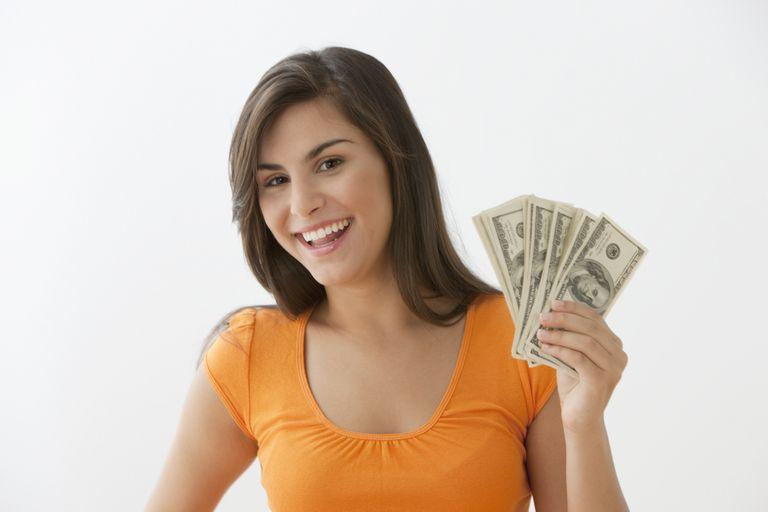 Caucasian teenage girl in orange shirt holding cash