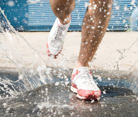 Runner stepping in puddle
