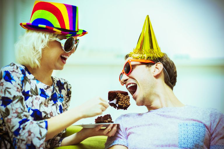Woman feeding a piece of cake to a man