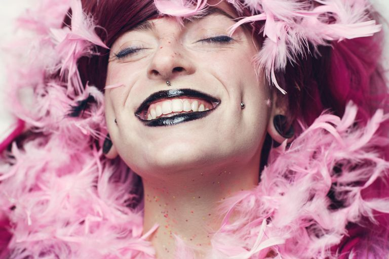 White woman with mauve hair surrounded by a pink feather boa, wearing black lipstick with dimple piercings, a medusa piercing, and stretched ears