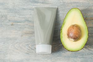 Tube of face mask and avocado