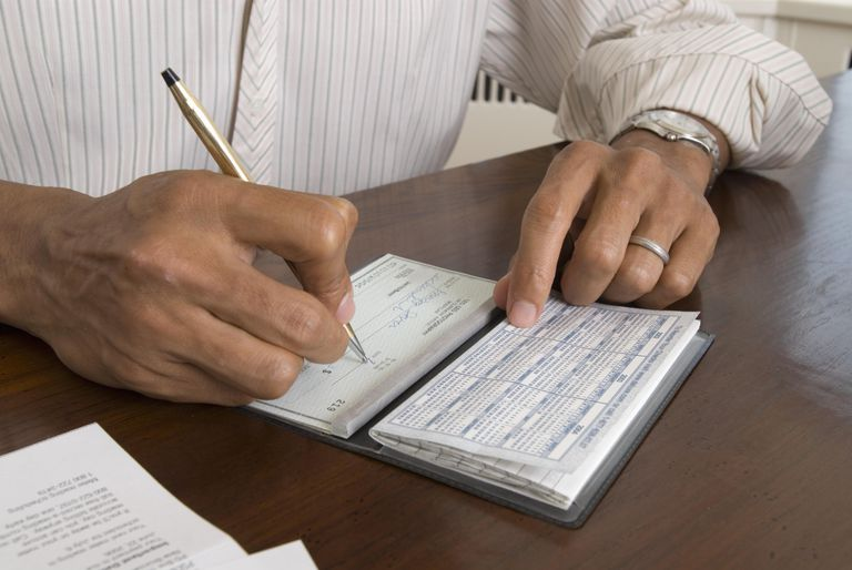Man at desk writing check, close-up