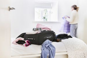 Woman packs winter holiday suitcase in the bedroom