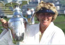Betsy King - in a robe after making the Champion's Leap - holds the trophy she earned for winning the 1997 Kraft Nabisco Championship.