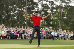 Tiger Woods celebrates after sinking his putt on the 18th green to win during the final round of the 2019 Masters.