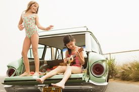 kids playing guitar in back of car