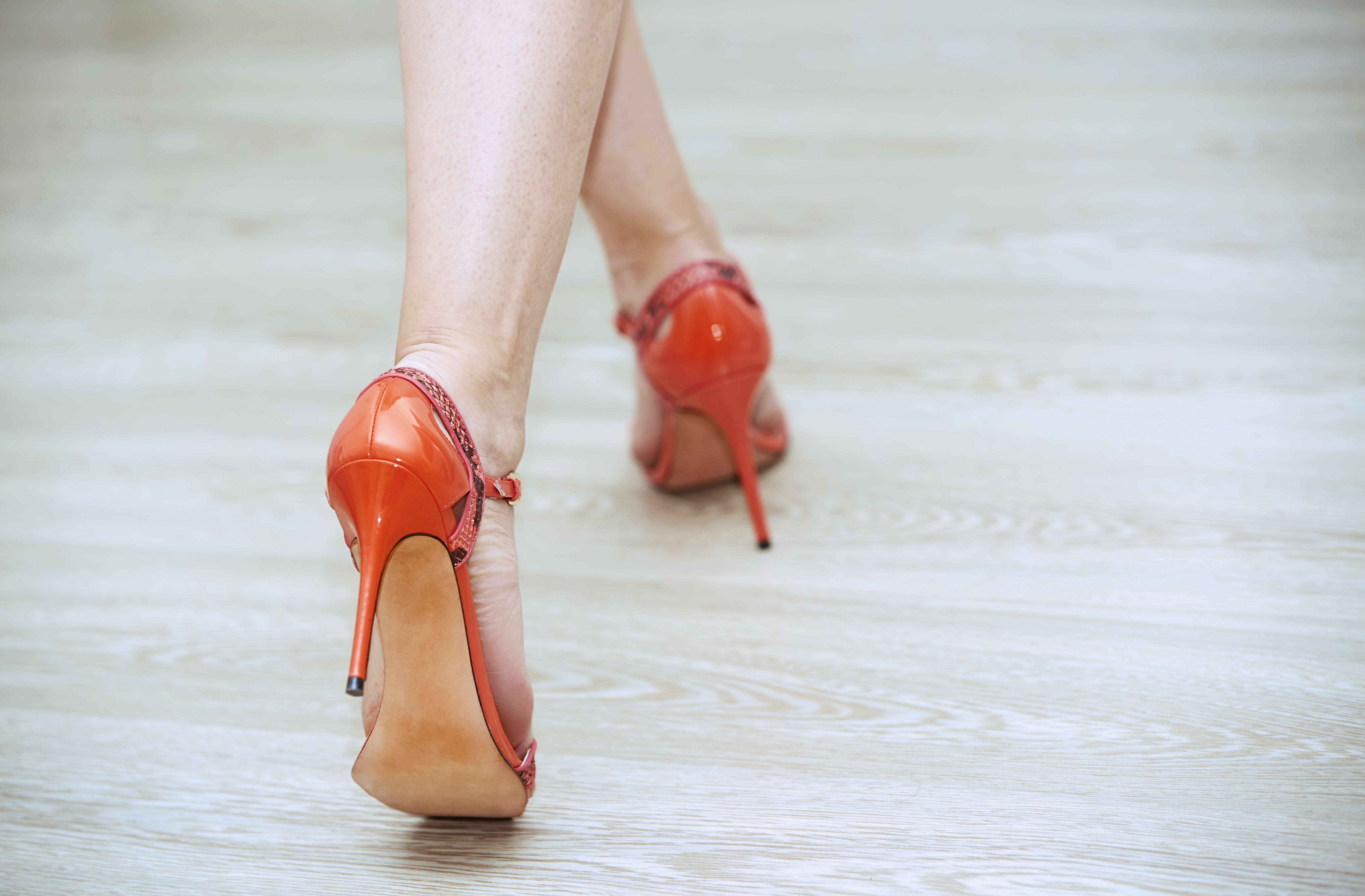 Legs of woman walking in red high heels