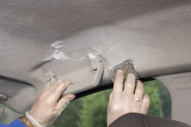 Hand wash of car headlamp. Hands in disposable gloves scrub the headliner