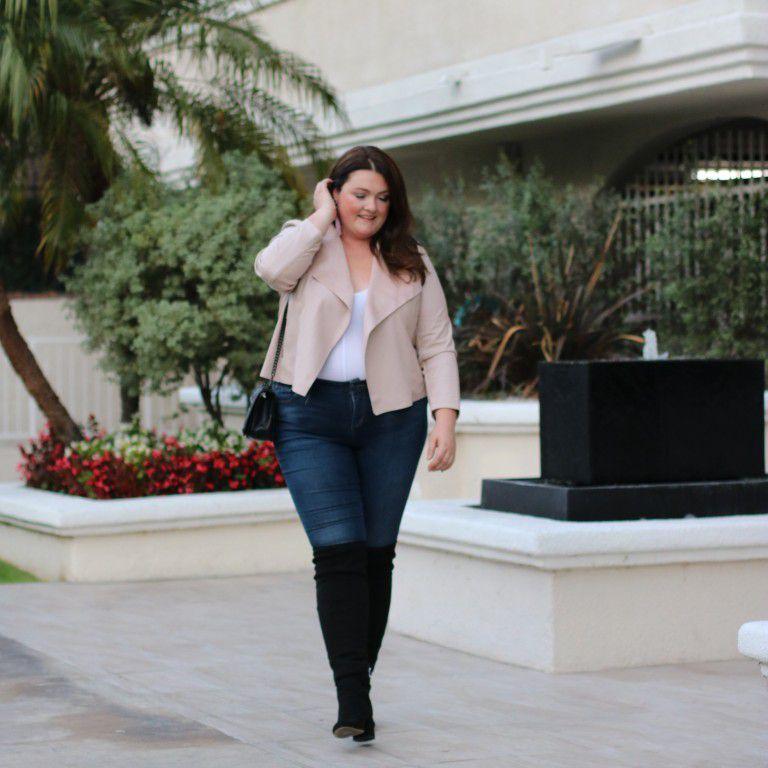 Woman in neutral blazer and dark wash jeans