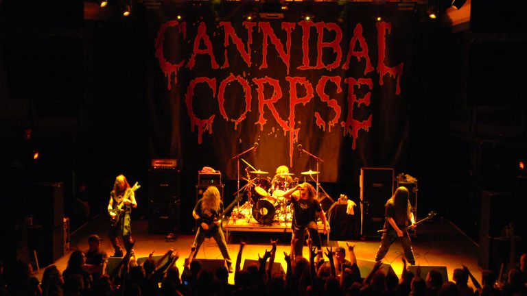 Cannibal Corpse performing live on stage before an audience.