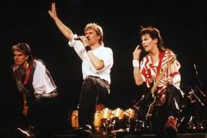 Bassist John Taylor (L), singer Simon Le Bon, and guitarist Andy Taylor of the British pop group Duran Duran performing on stage during a concert, 1984.