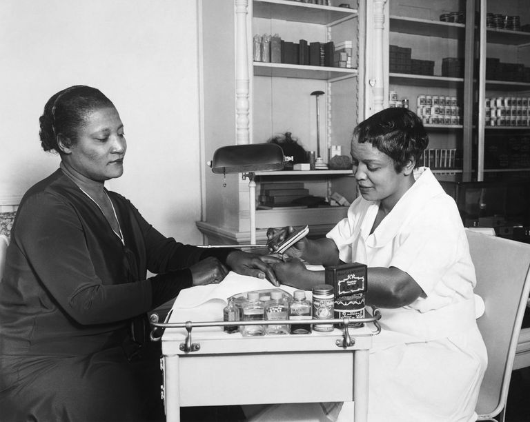 black and white photo of black woman getting her nails done