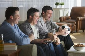 USA, New Jersey, Jersey City, three men watching television