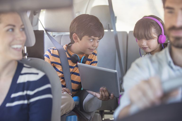 Brother and sister sharing digital tablet in back seat of car