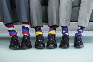 Men sitting on bench wearing colourful socks