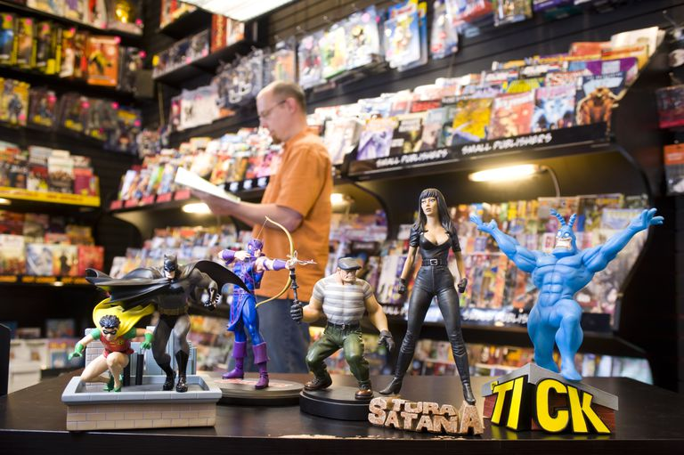 Comic book figurines and customer reading comic book at Newbury Comics.