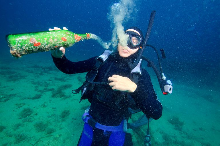 Scuba diver playing with a glass bottle underwater.