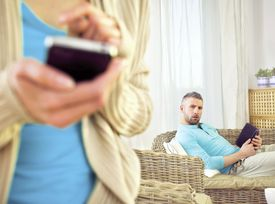 woman texting someone on cell phone, curious husband in the background sitting in a chair