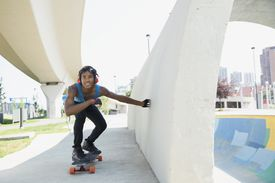 Teenage boy with headphones skateboarding along wall