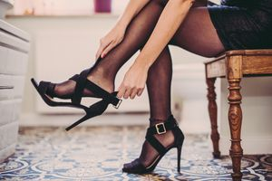 Woman getting ready for party with high heels and black dress