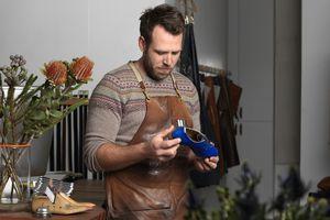 Shoemaker holding new shoe
