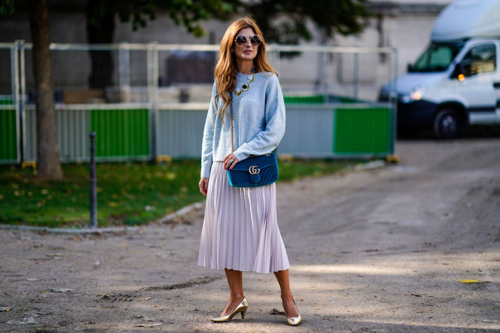 Woman wearing blue sweater and purple pleated skirt for street style fashion