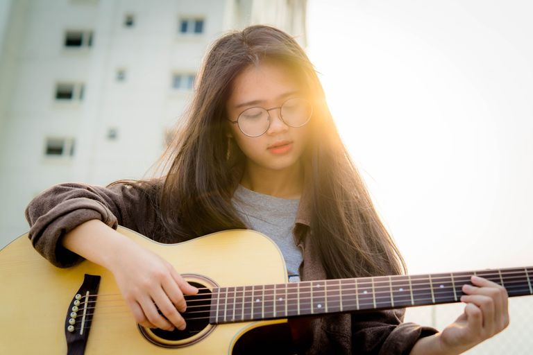 Young woman playing an acoustic guitar outside.