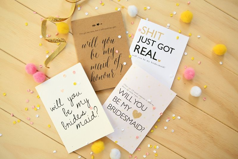 """Four """"Will You be My Bridesmaid?"""" cards on a table"""