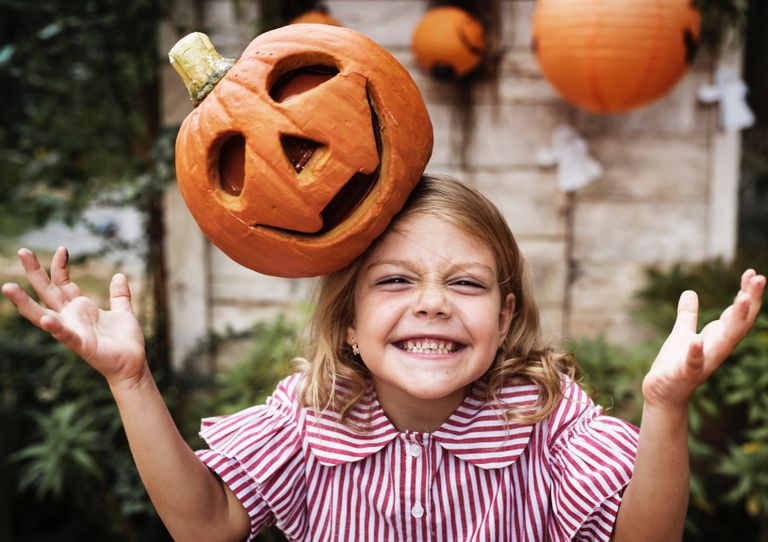 Young girl with a jack-o-lantern on her head grinning.