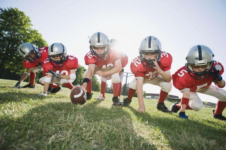 Football players at line of scrimmage ready to snap football