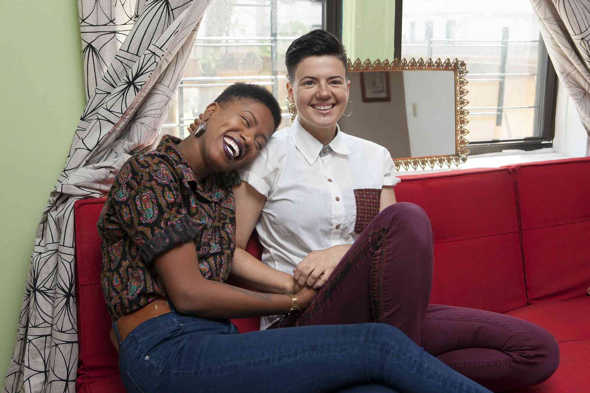 Lesbian couple holding hands on their sofa
