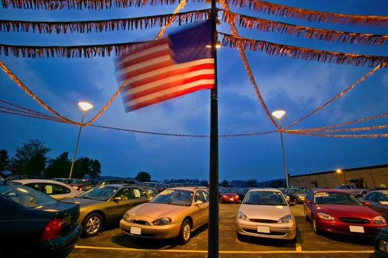 American flag fluttering in the wind at a car dealership